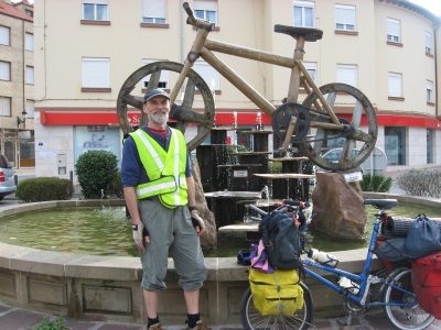 Picture of Peter Marsh in front of a wooden bike scuplture